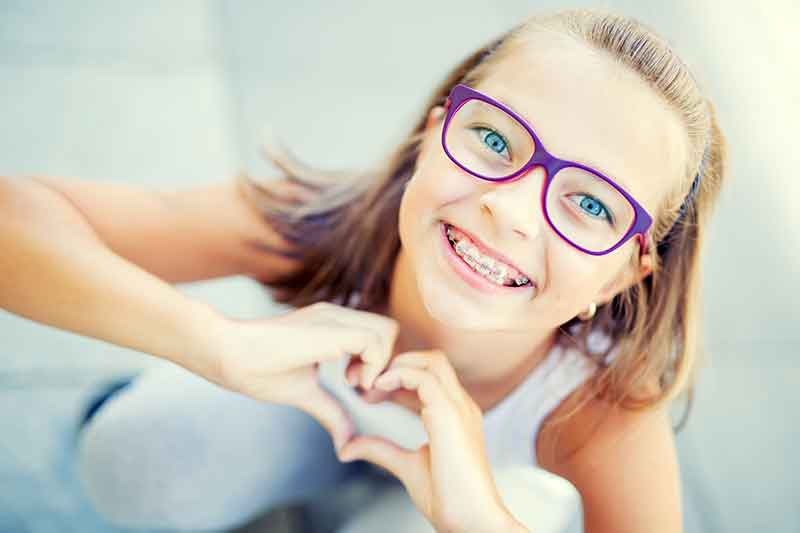 smiling-girl-with-braces-making-heart-shape-with-hands